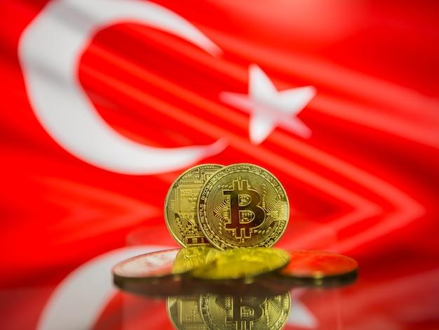 Moeda de ouro bitcoin e bandeira desfocada do fundo da turquia. conceito de criptomoeda virtual.