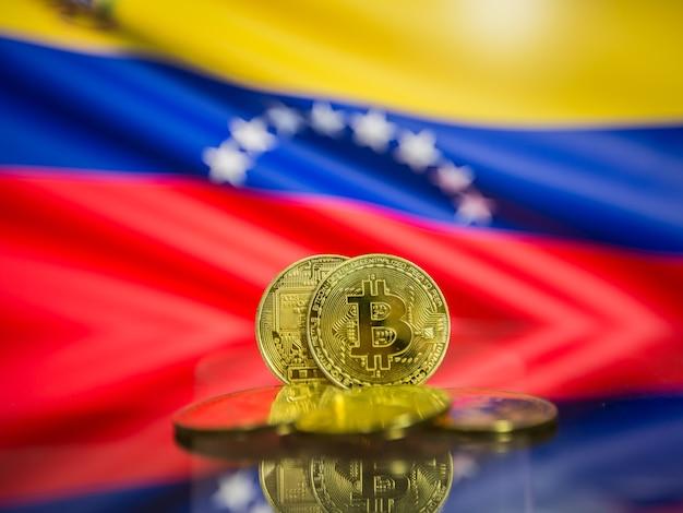 Moeda de ouro bitcoin e bandeira desfocada do fundo da venezuela. conceito de criptomoeda virtual.