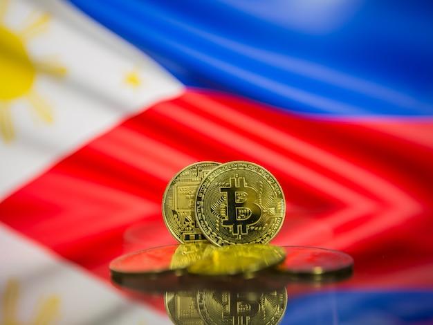 Moeda de ouro bitcoin e bandeira desfocada do fundo das filipinas. conceito de criptomoeda virtual.
