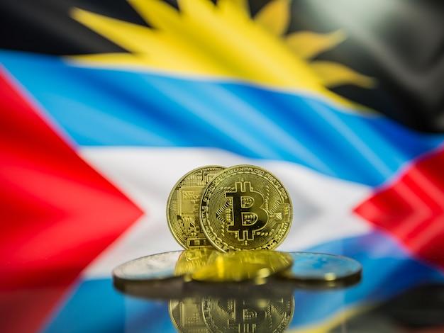 Moeda de ouro bitcoin e bandeira desfocada do fundo de antígua e barbuda.