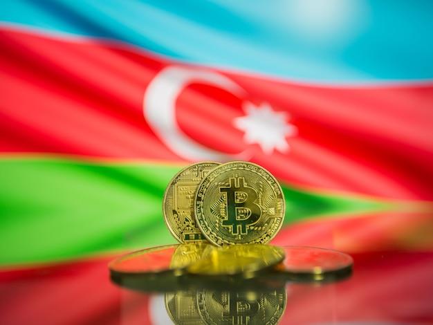 Moeda de ouro bitcoin e bandeira desfocada do fundo do azerbaijão. conceito de criptomoeda virtual.