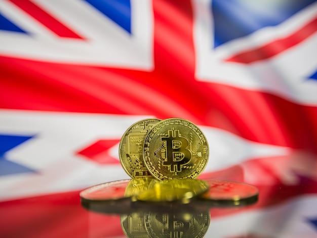 Moeda de ouro bitcoin e bandeira desfocada do fundo do reino unido. conceito de criptomoeda virtual.