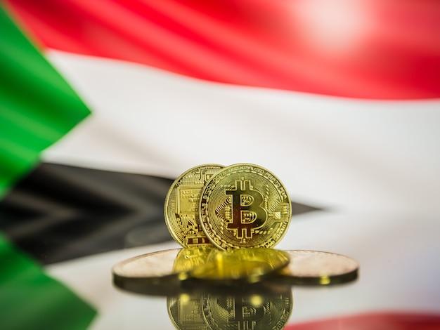 Moeda de ouro bitcoin e bandeira desfocada do fundo do sudão. conceito de criptomoeda virtual.