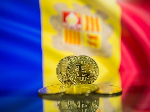 Moeda de ouro bitcoin e fundo desfocado da bandeira de andorra. conceito de criptomoeda virtual.