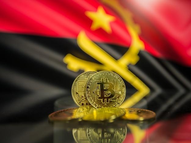 Moeda de ouro bitcoin e fundo desfocado da bandeira de angola. conceito de criptomoeda virtual.