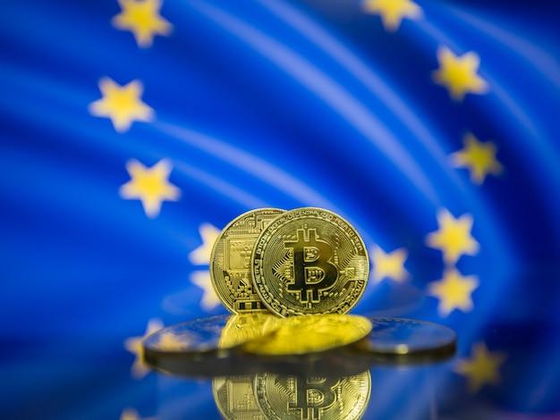 Moeda de ouro bitcoin e fundo desfocado da bandeira europeia. conceito de criptomoeda virtual.