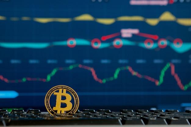 Moeda de ouro bitcoin e gráfico desfocado