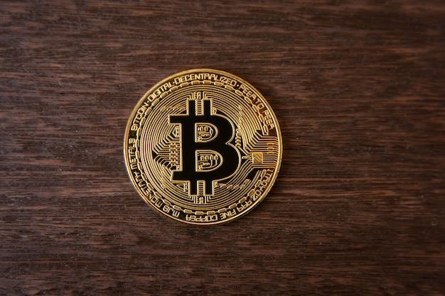 Moeda de ouro bitcoin em madeira escura