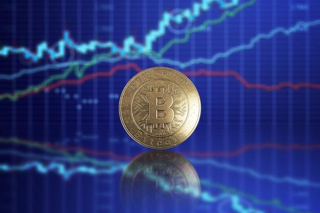 Moeda de ouro bitcoin em um fundo de gráficos de negócios
