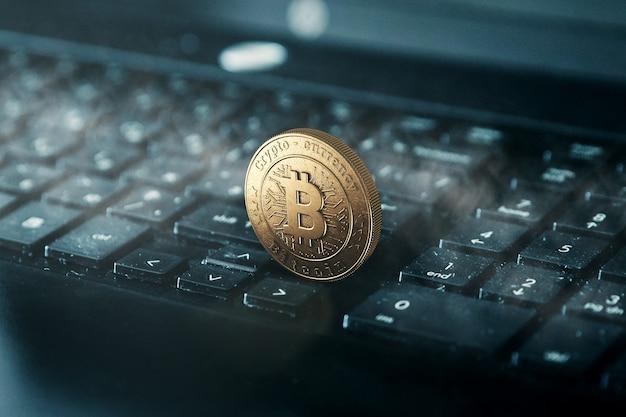 Moeda de ouro bitcoin em um teclado preto.