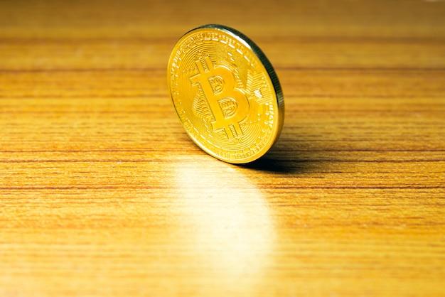 Moeda de ouro brilhante na mesa de madeira.