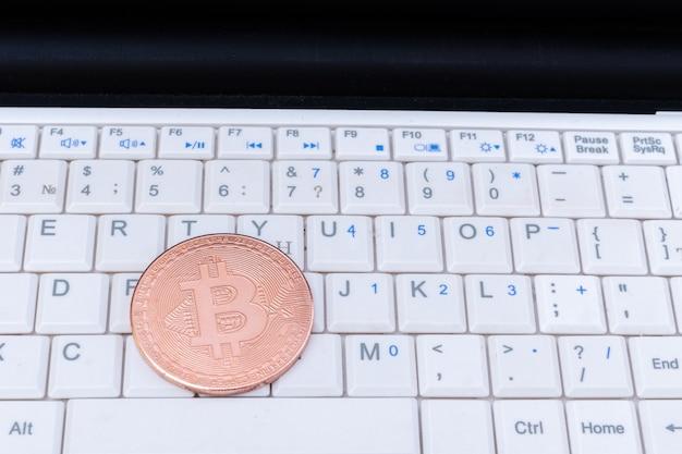 Moeda de ouro da criptomoeda bitcoin em um teclado de laptop. crise financeira. dinheiro digital. tecnologia blockchain. conceito de criptomoeda virtual
