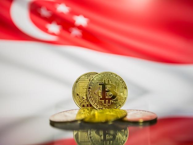Moeda de ouro de bitcoin e bandeira desfocada de fundo de cingapura. conceito de criptomoeda virtual.