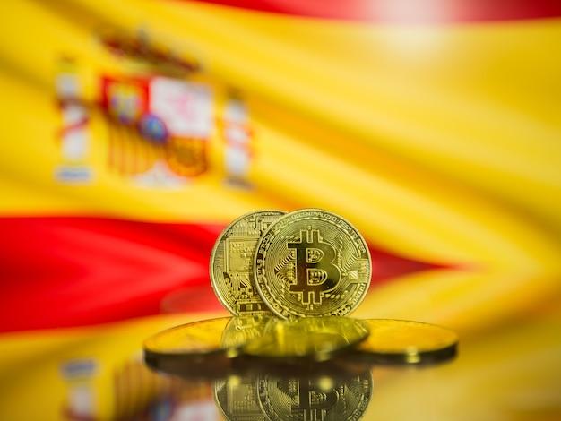 Moeda de ouro de bitcoin e bandeira desfocada de fundo de espanha. conceito de criptomoeda virtual.