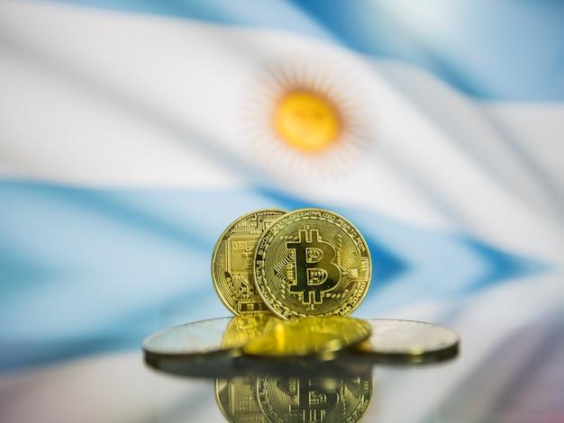 Moeda de ouro de bitcoin e bandeira desfocada do fundo da argentina. conceito de criptomoeda virtual.