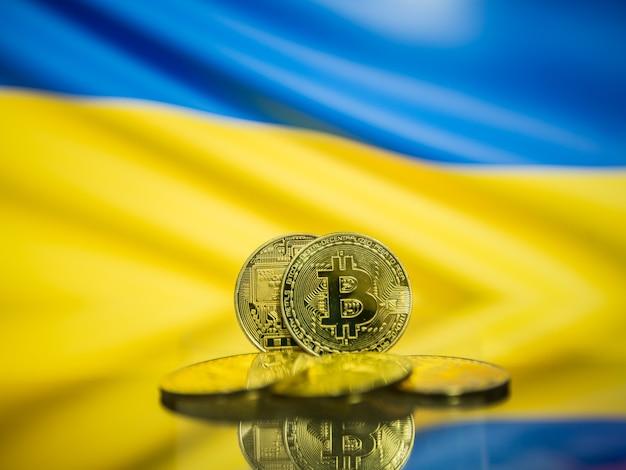 Moeda de ouro de bitcoin e bandeira desfocada do fundo da ucrânia. conceito de criptomoeda virtual.
