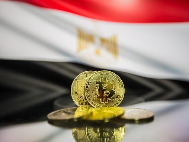 Moeda de ouro de bitcoin e bandeira desfocada do fundo do egito. conceito de criptomoeda virtual.