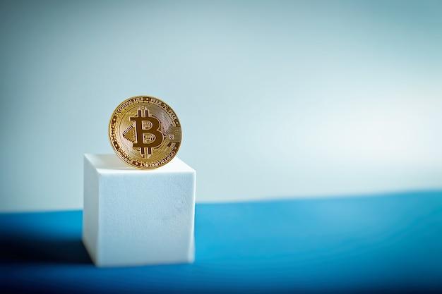 Moeda de ouro de bitcoin e plano de fundo desfocado do gráfico.