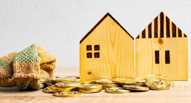 Moeda de ouro no saco de cânhamo e duas casas na mesa com espaço para cópia