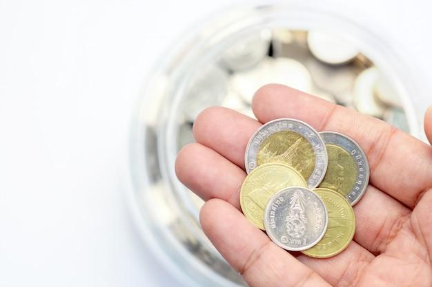 Moeda de prata do ouro baht tailandês na mão com moedas de garrafa de vidro blur
