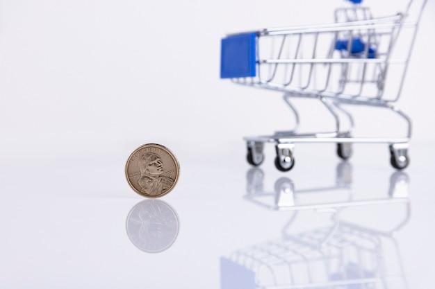 Moeda de um dólar americano no fundo de um carrinho de supermercado em um fundo branco. copie o espaço. foco seletivo