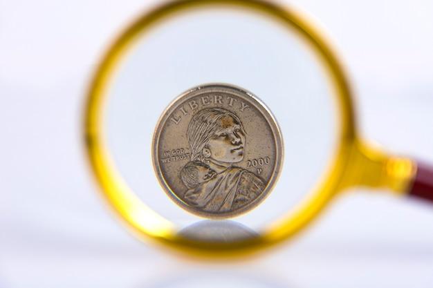 Moeda de um dólar americano por meio de uma lupa em um fundo branco. copie o espaço. foco seletivo