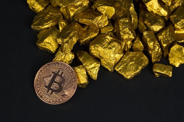 Moeda digital de bitcoin e pepita de ouro sobre fundo preto