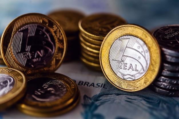 Moeda do brasil mais notas de 100 reais em cenário escuro, conceito de crise financeira