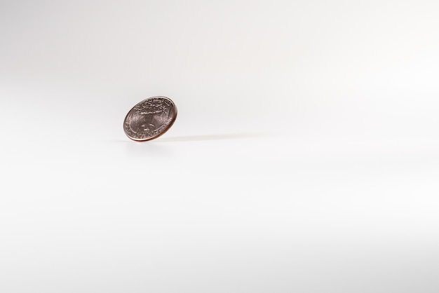 Moeda do dólar que gira no fundo branco, conceito da economia americana.
