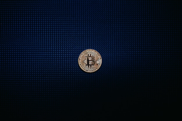 Moeda dourada do bitcoin isolada na obscuridade azul