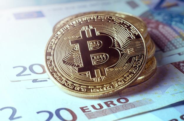 Moeda física de bitcoin do ouro de encontro às euro- contas.