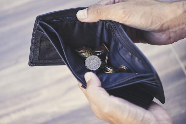 Moeda no conceito de gestão de carteira e dívida - carteira vazia nas mãos de um homem idoso pobreza no conceito de aposentadoria