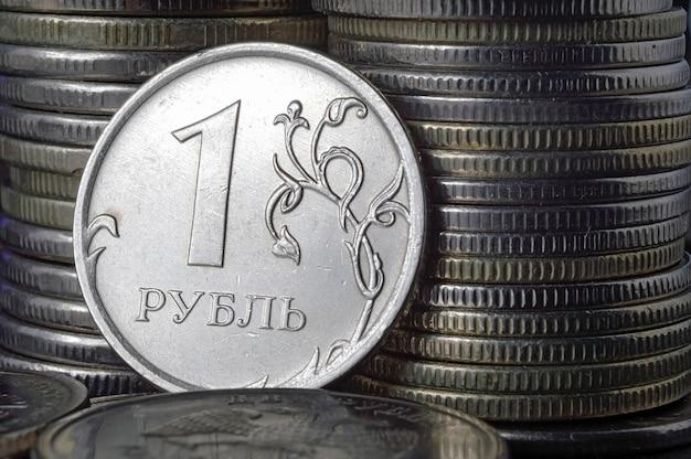 Moeda russa de 1 rublo (reverso) contra outras moedas dobradas em colunas.