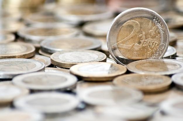 Moeda suja de 2 euros com moedas no fundo
