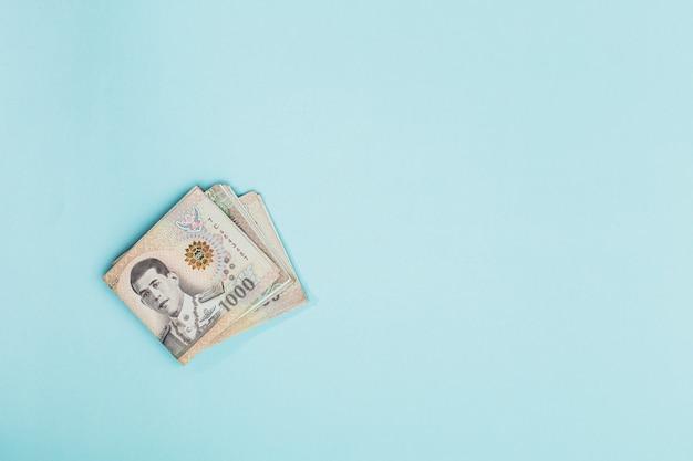 Moeda tailandesa, 1000 baht, notas de dinheiro da tailândia sobre fundo azul com espaço de cópia para o conceito de negócios e finanças