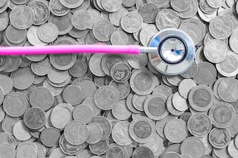 Moeda tailandesa do conceito do negócio do fundo, moeda do dinheiro da finança da saúde do estetoscópio no fundo branco