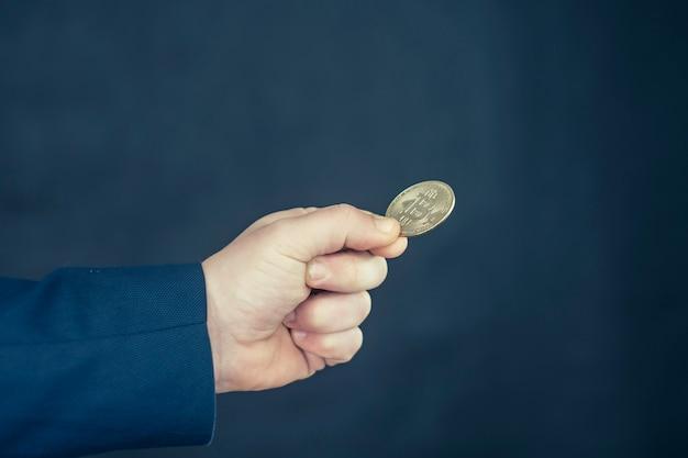 Moeda virtual e conceito de blockchain. empresário com uma jaqueta azul com bitcoin nas mãos.