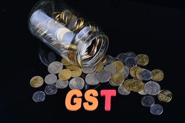 Moedas caindo de um pote de dinheiro com a palavra gst
