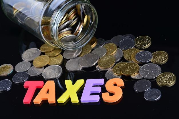 Moedas caindo de um pote de dinheiro com a palavra impostos