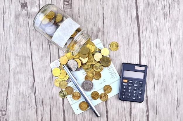 Moedas, calculadora e caneta no livro de contas bancárias com etiqueta em branco