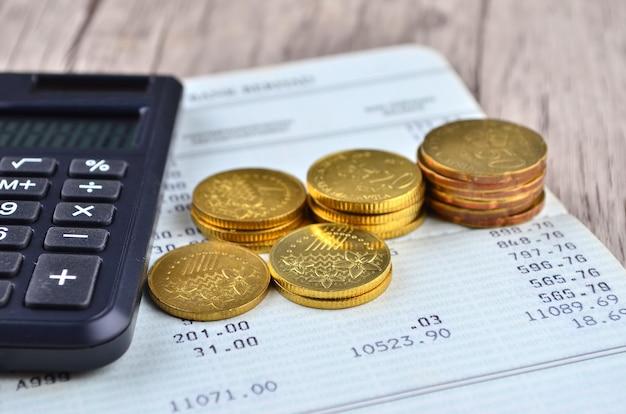Moedas, calculadora e caneta no livro de contas bancárias
