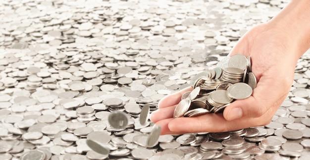 Moedas colocadas em cima. enquanto a mão de um homem derramando moedas