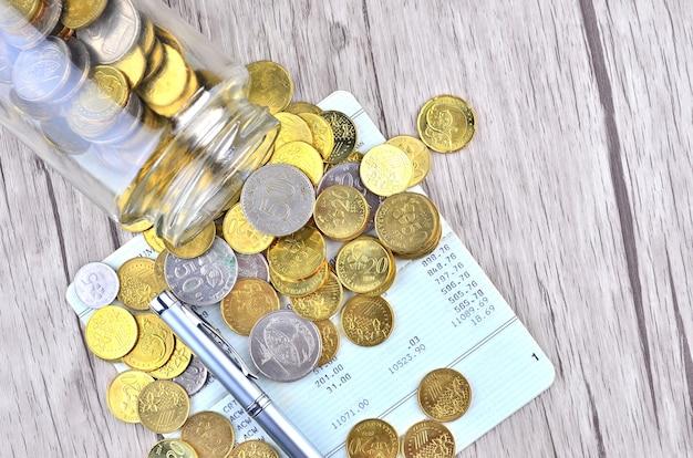 Moedas com caneta de prata no livro de contas bancárias