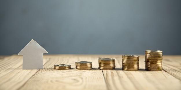 Moedas com casa de papel. conceito de hipoteca de investimento