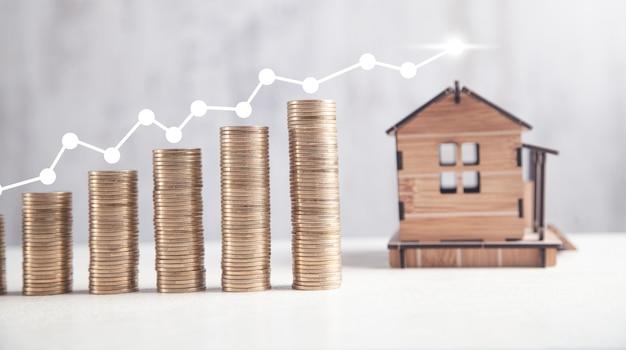 Moedas com modelo de casa. gráfico imobiliário. crescimento do mercado doméstico