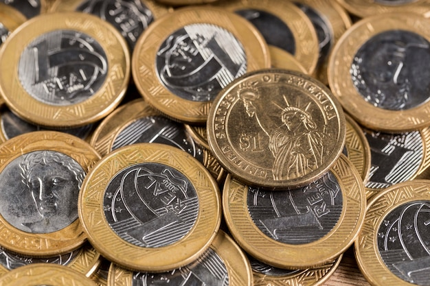 Moedas de 1 dólar no meio de várias moedas de 1 real em uma mesa de madeira