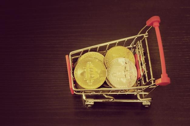 Moedas de bitcoin no carrinho de compras. fundo preto. vista do topo