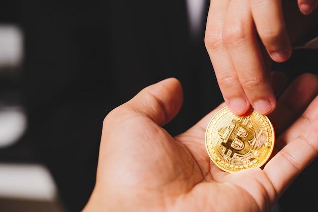 Moedas de criptomoeda bitcoin, as mulheres seguram a moeda de criptomoeda na mão. troca de dinheiro