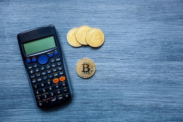 Moedas de criptomoeda bitcoin de ouro e calculadora em fundo de madeira