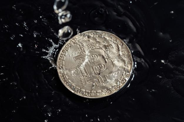 Moedas de criptomoeda em um fundo escuro. foto macro. gotas de chuva nas moedas.